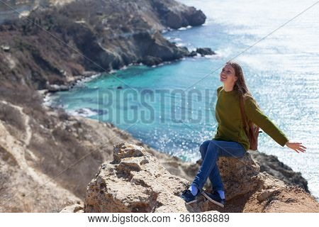 Attractive Young Woman With A Backpack On A Trip In The Background Of A Sea Bay. The Concept Of Trav