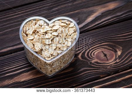 One Heart Of Oat-flakes, Uncooked Oats On Brown Wooden Board Background. Laconic Design. Symbol Of L