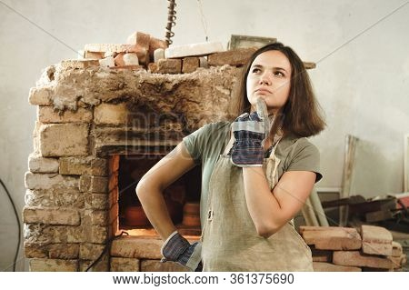 Potter Girl With Apron In Workshop On Background Of Pottery Kiln. Female Mastery Concept.