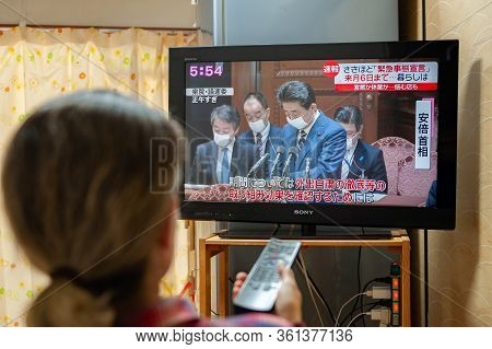 Fuji City, Shizuoka, Japan - April 7, 2020: A Woman Watches Japan Pm Shinzo Abe On Tv About The Decl