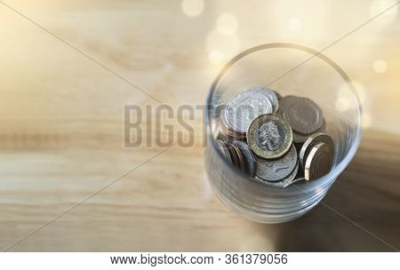 Top View New One Pound British Sterling Coin And Penny And In Glass Bottle On Wooden Table, Concept