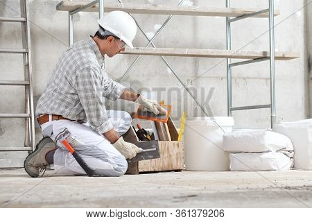 Plasterer Man Construction Worker Takes The Plaster Trowel From The Toolbox Wear Gloves, Hard Hat An
