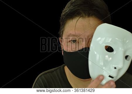 Man Wearing Cotton  Hygiene Mask And White Plastic Disguise Mask Isolated On Black Background