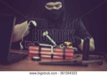 Masked Terrorist Preparing An Explosive Device With A Soldering Iron In Hand, Indoors On The Table: