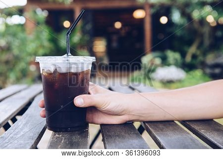 Cropped Shot Of Someone Hand Touching A Plastic Cup Of Iced Americano (black Coffee) On The Wood Pla