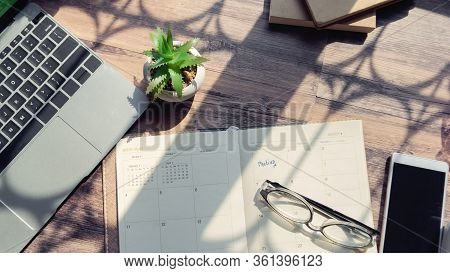 Working Online At Home Concept.laptop Smartphone Glasses Cactus And Diary Placed On Office Desk.cale
