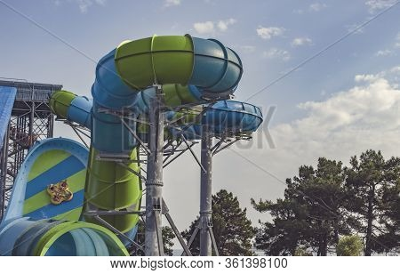 Big High Waterslide For Extreme Descents. People Slide Along The Wall At High Speed On A Large Infla