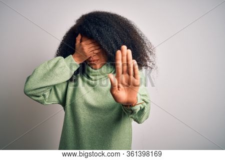 Young beautiful african american woman with afro hair wearing green winter sweater covering eyes with hands and doing stop gesture with sad and fear expression. Embarrassed and negative concept.