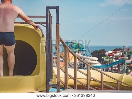 Closed Yellow Water Slide On The Background Of The Water Park. The Man Before The Descent. A Man Pre