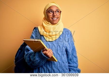 Young African American student woman wearing muslim hijab and backpack holding book smiling looking to the side and staring away thinking.