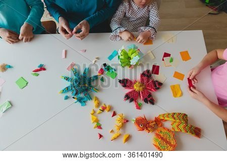 Family Making Origami Crafts With Paper, Father And Kids Stay Home