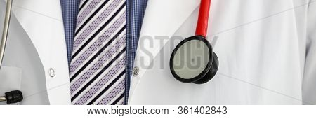 Stethoscope Lying On Male Therapeutist Doctor Chest Wearing Necktie. Medical Care Help Or Insurance