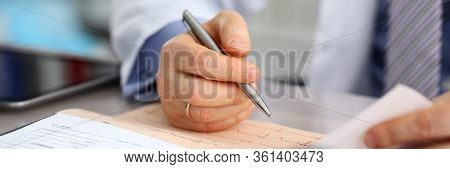 Male Doctor Hands With Cardiogram Chart On Clipboard Pad Fill Medical History With Silver Pen. Cardi