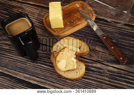 Fresh Wheat Toast With Butter, A Ceramic Mug Of Coffee With Milk And A Piece Of Butter In A Wooden B