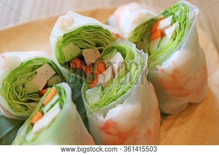 Closeup Delectable Fresh Vegetables With Prawn Spring Rolls On A Wooden Plate