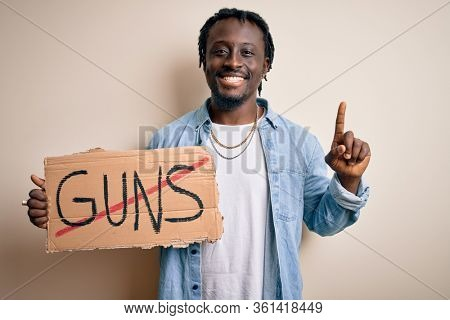 Young african american man asking for peace holding banner with prohibited guns message surprised with an idea or question pointing finger with happy face, number one