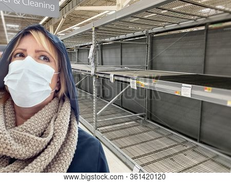 Young Woman Wearing Medical Face Mask In Empty Aisle of Grocery Store.