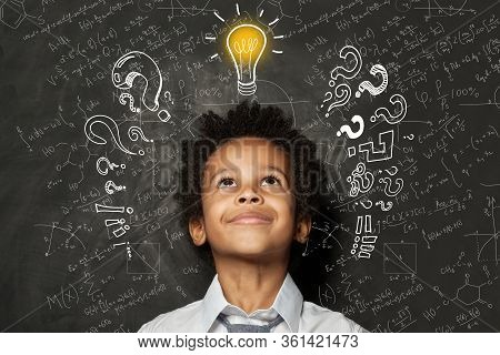 Smart Black Kid With Lightbulb. Brainstorming And Idea Concept. Little Student Boy On Chalkboard Bac