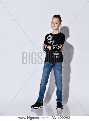 Teenage Boy In Black Jumper With Inscriptions And Sneakers, Blue Jeans, Bracelet. He Standing With F