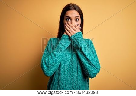 Young beautiful brunette woman wearing green casual sweater over yellow background shocked covering mouth with hands for mistake. Secret concept.