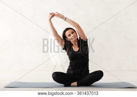 Yoga meditation at home. Beautiful young woman working out in home interior, doing yoga or pilates exercises