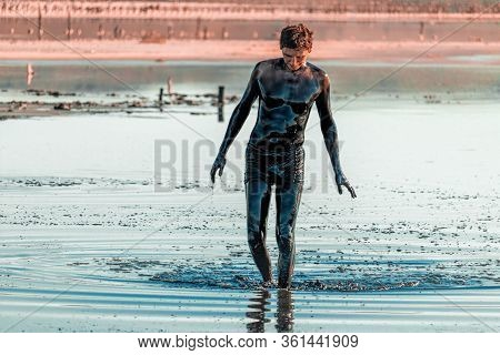 Man Applying Black Healing Clay. Mud Spa On The Shore Of Salt Lake. Swimming In The Nutrient-rich Mu