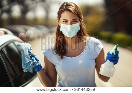 A Young Woman With A Mask On Her Face And Protective Gloves On Her Hands Is Ready To Wipe Her Car Ho