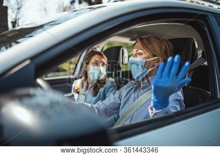 Young Business Women With Protective Masks On Their Faces Are Going To The Work Together By Car And