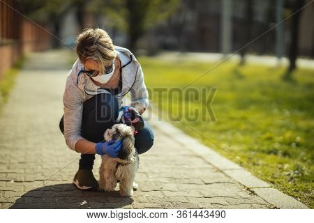 A Woman In A Medical Protective Mask Is Walking Along The City Street Path With Her Dear Cute Little