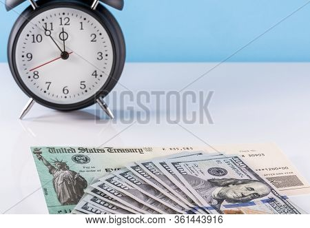 Stack Of 100 Dollar Bills With Illustrative Coronavirus Stimulus Payment Check And Alarm Clock To Sh