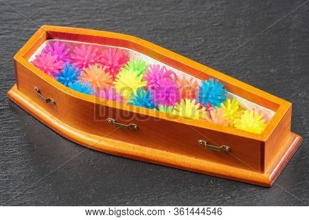 Small Wooden Coffin Coffin Filled With Multicolored Coronovirus Models. Covid 19 Pandemic Concept