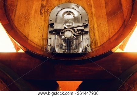 Old Historic Wine Cellar In Langhe (piedmont, Italy). Detail Of A Stainless Steel Valve On An Oaken