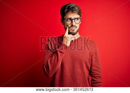 Young handsome man with beard wearing glasses and sweater standing over red background with hand on chin thinking about question, pensive expression. Smiling with thoughtful face. Doubt concept.