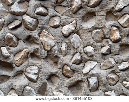 Stucco With Pebbles Closeup. Gray Uneven Cement Covered With Large Pebbles. Background With Stucco A