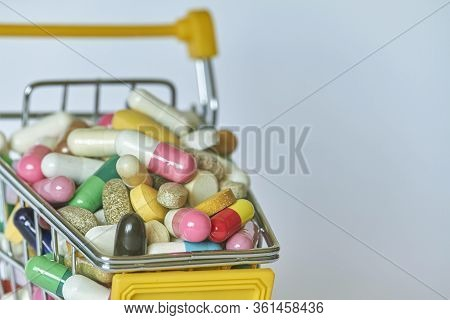 Medical Background Or Concept. Close-up Of A Shopping Trolley Filled With Colorful Pills. Cart From