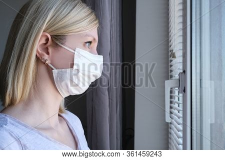 Scared Woman In Surgical Face Mask Staying At Home And Looking Through The Window, Covid-19 Quaranti
