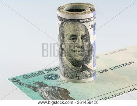 Roll Of 100 Dollar Bills With Illustrative Coronavirus Stimulus Payment Check To Show The Virus Stim