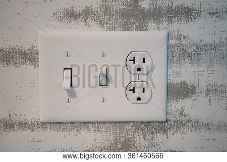 Electrical Outlet Socket With Light Switches And Grounded North American Plugs.
