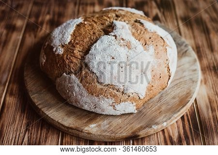 Grain Artisan Bread Loaf. Rustic Loaf Of Homemade Bread On Dark Wooden Table. Homemade Loaf Of Bread