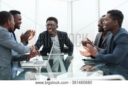 project Manager explaining something to employees at an office meeting