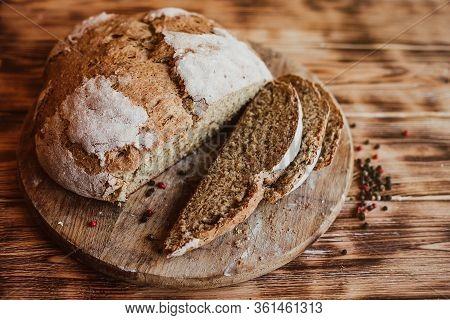 Grain Artisan Bread Loaf. Rustic Loaf Of Homemade Bread Sliced On Dark Wooden Table. Homemade Loaf O
