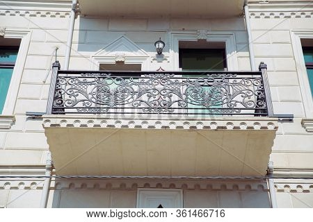 Window Balcony On A Stone Building . Elegant Decorative Old Stone Balcony. Low Level Perspective Of
