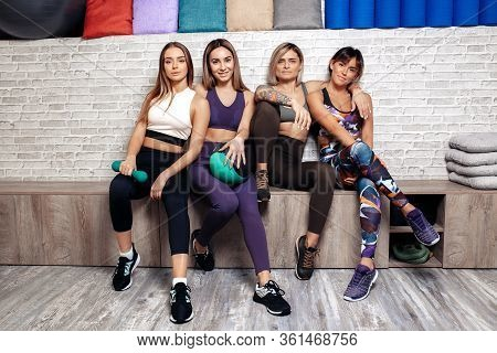 Group Of Four Young Fit Girls Standing Together Relaxing After Workout In Fitness Class.