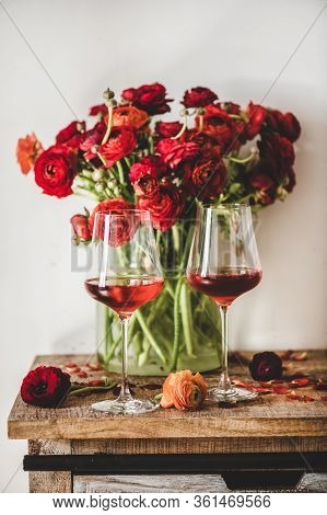 Rose Wine In Glasses And Red Flowers Over Wooden Table
