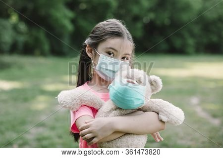 Stress Little Girl Holding Toy Bear In Medical Protective Mask