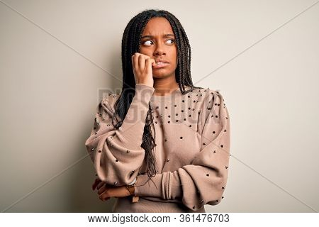 Young african american fashion woman standing casual over brown isolated background looking stressed and nervous with hands on mouth biting nails. Anxiety problem.