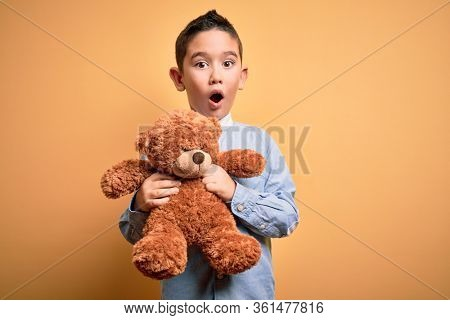Young little boy kid hugging teddy bear stuffed animal over yellow background scared in shock with a surprise face, afraid and excited with fear expression