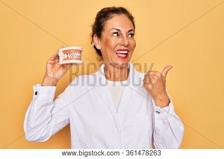 Middle age senior dentist woman holding orthodontics denture with braces aligner pointing and showing with thumb up to the side with happy face smiling