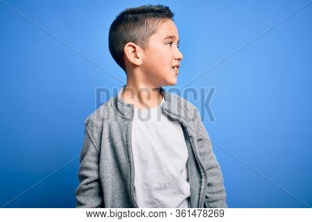Young little boy kid wearing sport sweatshirt over blue isolated background looking away to side with smile on face, natural expression. Laughing confident.