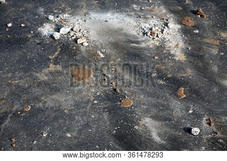 Backgrounds and Textures. Cement, Dirt and Broken Concrete pieces on a blacktop drive way. Construction Site. Demolition Site with Cement and Dirt Residue.